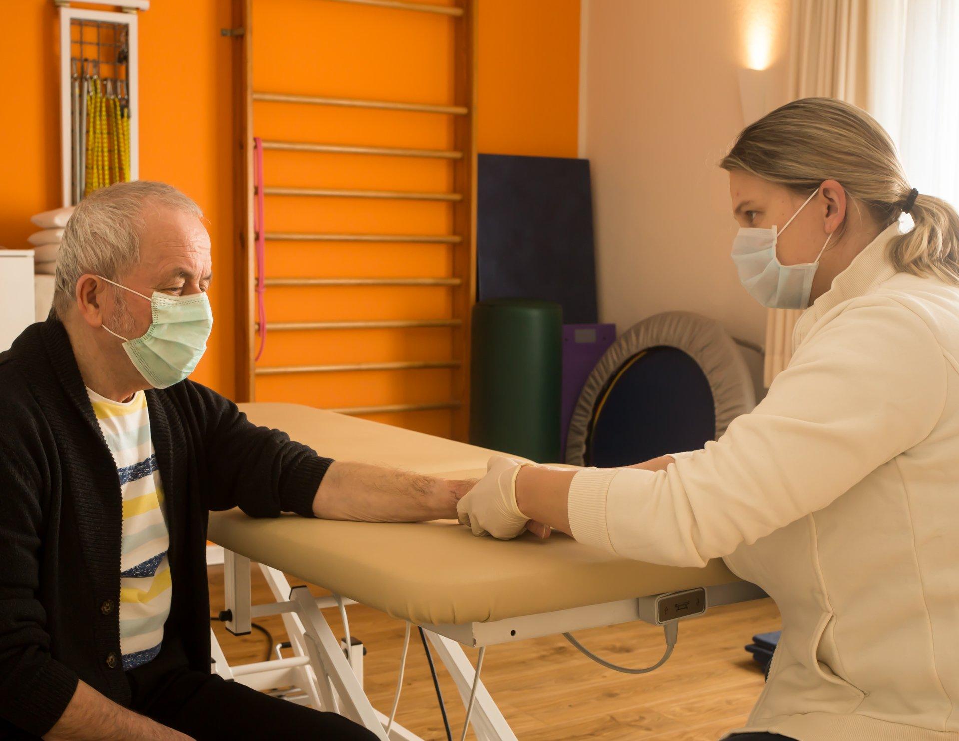 Anschlußbehandlung nach der Operation: Physiotherapeutin Sandra Okafor behandelt die Hand eines Patienten - Foto: Anna Bless
