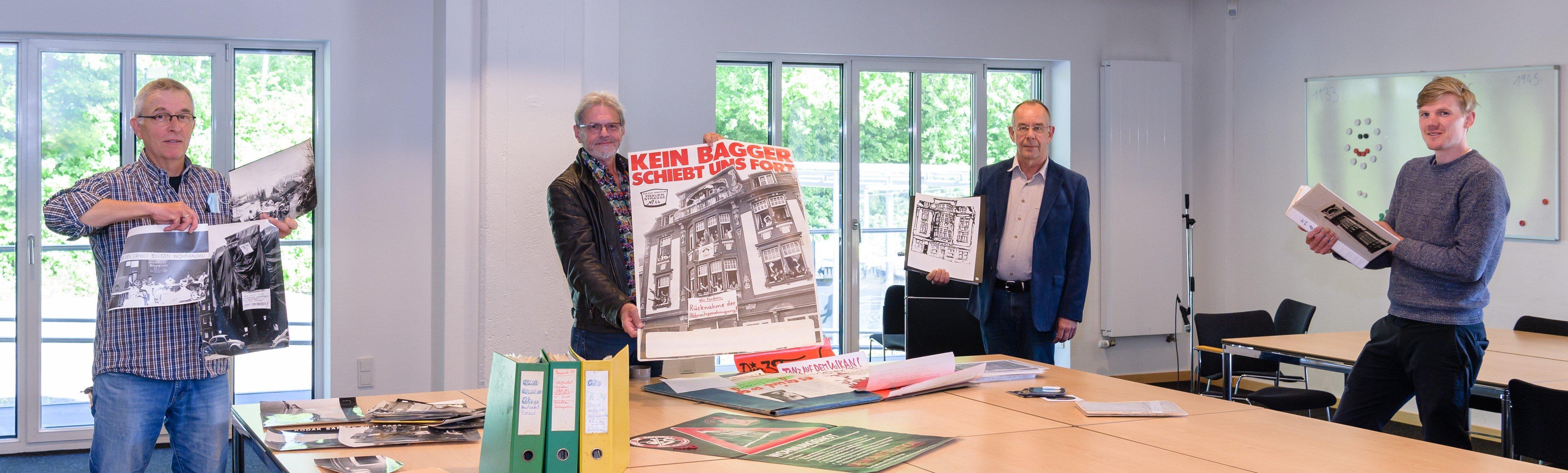 Vom Protest zum Archivgut (v.l.): Joachim Kämper, Bernd Uppena (ehemalige Haussprecher) und Dr. Joachim Hetscher (Kulturverein Frauenstraße) übergeben dem Stadtarchiv mit Dr. Philipp Erdmann einen umfangreichen Nachlass.  Foto: Presseamt Münster.