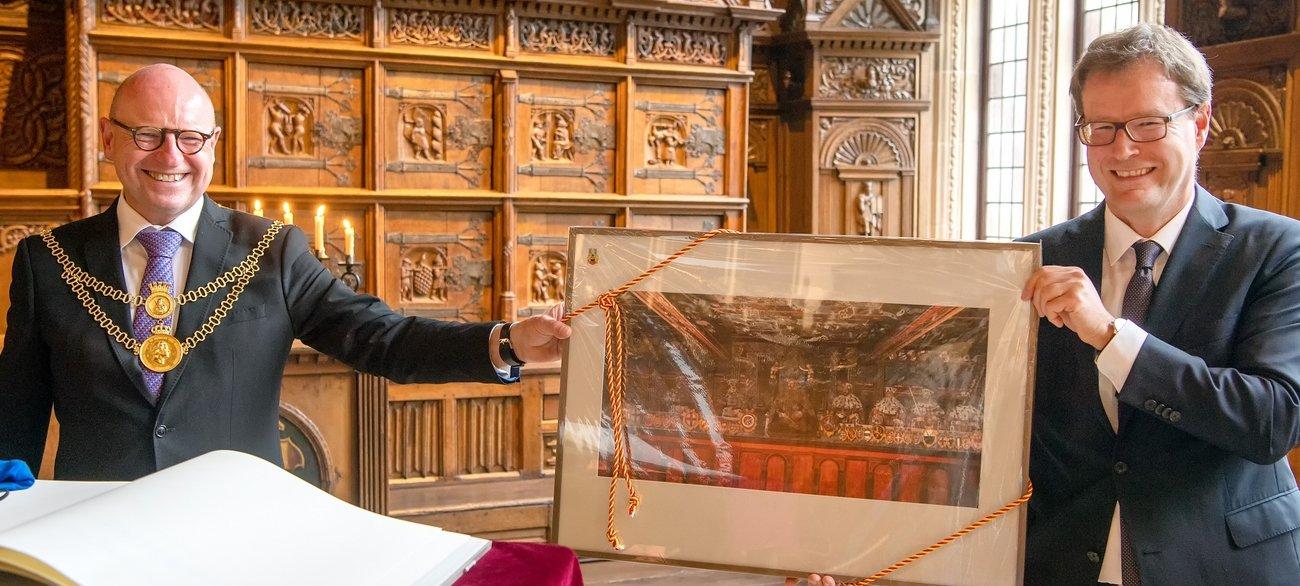 Foto: Geschenk unter Freunden: Oberbürgermeister Markus Lewe freut sich über eine Reproduktion, die Amtskollege Dr. Johannes Bruns aus Thüringen mitgebracht hat. Sie zeigt die Wandmalerei im historischen Mühlhäuser Rathaus. Foto: Presseamt  Münster / Wolfram Linke.