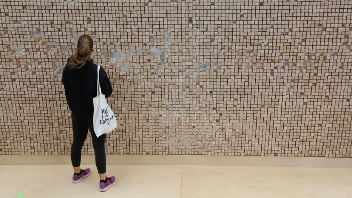 Segovia: Anfangs gleicht die Verschwindende Wand einer dichten Mauer... © Celia de Coca Die Verschwindende Wand in Segovia ...dann ziehen die ersten Besucher die Holzklötze aus der Wand ... © Celia de Coca Die Verschwindende Wand in Segovia ...entdecken die Inschriften... © Celia de Coca Die Verschwindende Wand in Segovia ...immer mehr Menschen kommen und stöbern - mit Abstand - durch die Zitate.... © Celia de Coca Die Verschwindende Wand in Segovia ... bis die Menschen auf der anderen Seite sichtbar werden © Celia de Coca